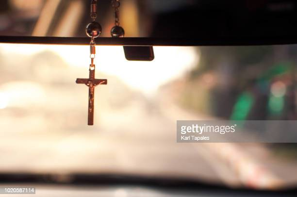 a rosary cross on the dashboard mirror of a car on the road - catholicism stock pictures, royalty-free photos & images