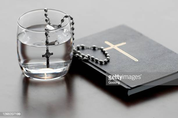 Rosary, glass of water, and holy Bible during Lent. A solemn religious observance that begins on Ash Wednesday and ends on Holy Saturday.