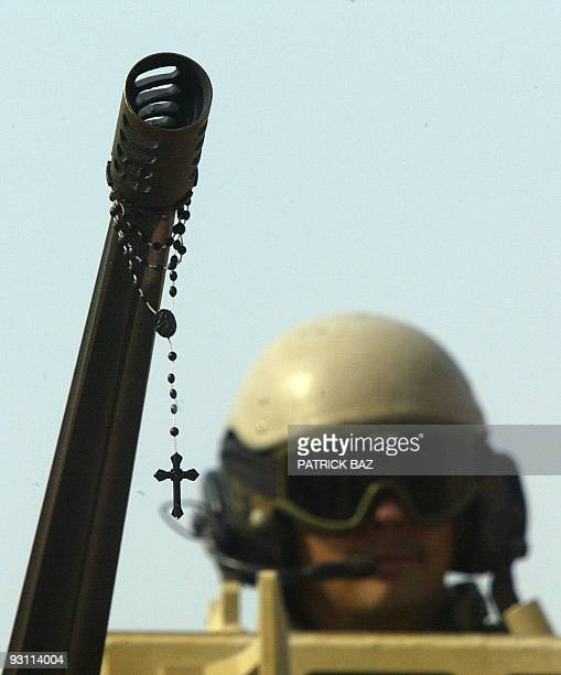 A rosary hangs off the barrel of a machinegun mounted on a Bradley belonging to the 1st Cavalry Regiment 5th Battalion positioned on the outskirts of...
