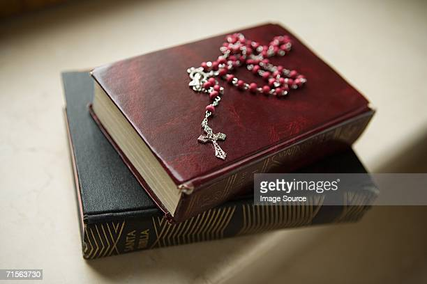 rosary on bibles - rosary beads stock pictures, royalty-free photos & images