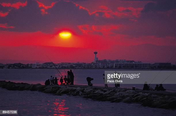 Rosas seaport People fish at sunset in the port of Roses Gerona province