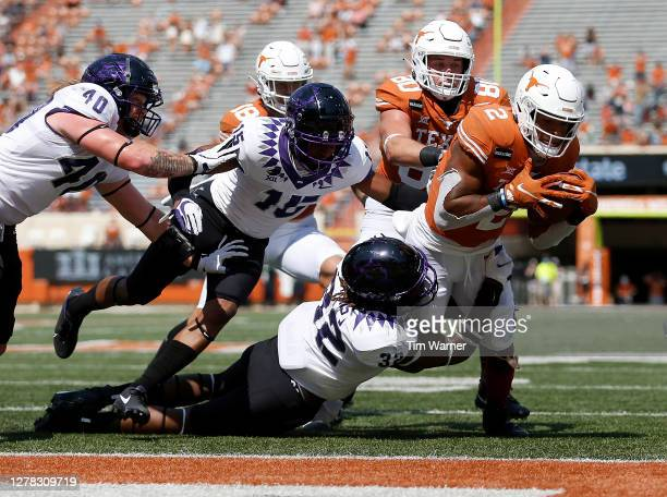 Roschon Johnson of the Texas Longhorns dives for a touchdown in the third quarter while defended by Ochaun Mathis of the TCU Horned Frogs at Darrell...