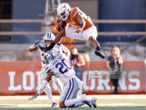 Roschon Johnson of the Texas Longhorns hurdles Denzel Goolsby of the Kansas State Wildcats in the third quarter at Darrell K RoyalTexas Memorial...