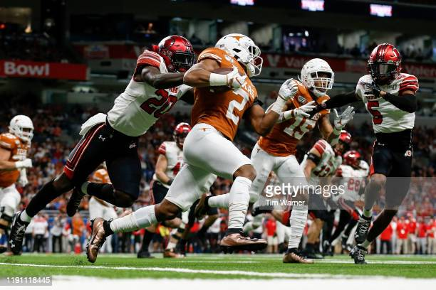 Roschon Johnson of the Texas Longhorns runs the ball defended by Devin Lloyd of the Utah Utes and Tareke Lewis in the first quarter during the Valero...