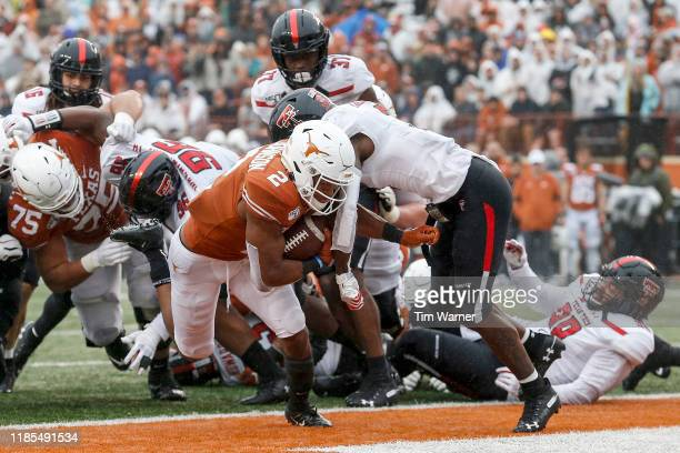 Roschon Johnson of the Texas Longhorns rushes for a touchdown in the second quarter defended by Douglas Coleman III of the Texas Tech Red Raiders at...