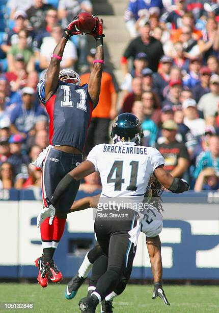 Roscoe Parrish of the Buffalo Bills makes a catch above Rashean Mathis and Tyron Brackenridge of the Jacksonville Jaguars at Ralph Wilson Stadium on...