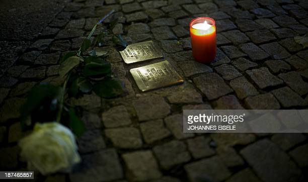 """Rose and a candle lay on a """"stolperstein"""" or stumbling stone during a walk on occasion of the 75th anniversary of the Nazi pogrom Kristallnacht of..."""