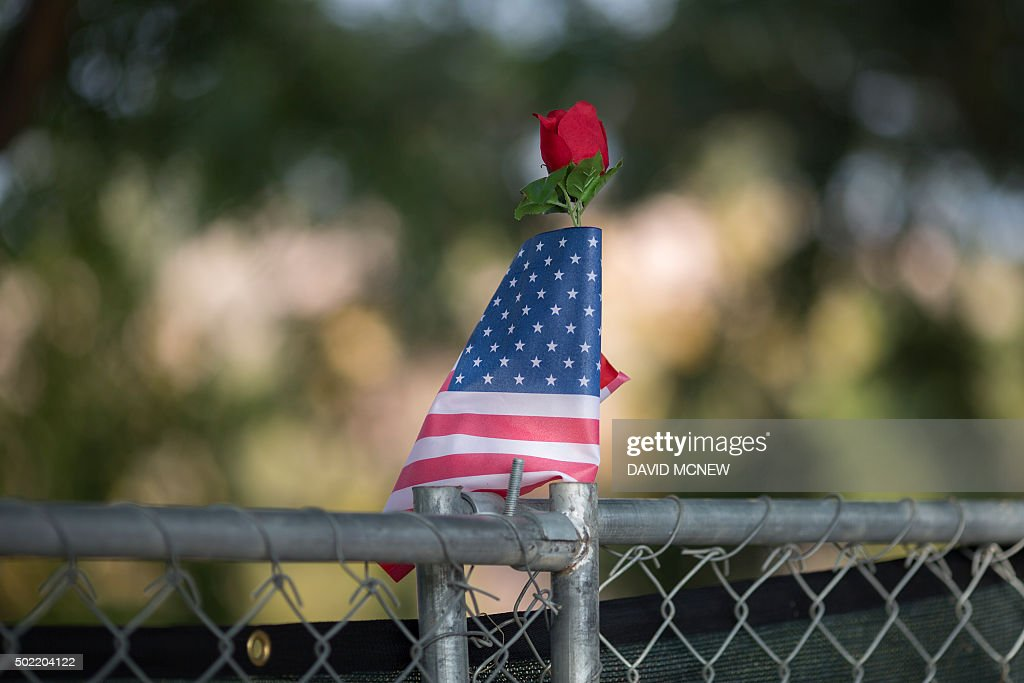 TOPSHOT - A rose and flag stand atop a fence surrounding the perimeter of the Inland Regional Center, site of the massacre by suspects Syed Farook and Tashfeen Malik earlier this month, in San Bernardino, California, December 21, 2015. Enrique Marquez, who is alleged to have purchased the assault rifles used by the couple to kill 14 people and injure many others, appeared at a detention hearing in federal court today. / AFP / DAVID