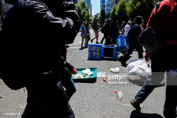 Rose City Antifa members push down garbage cans and roadside newspaper stands as they march towards Pioneer Courthouse Square to demonstrate against...