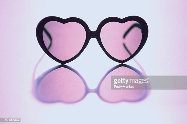 Rose Colored Glasses Sit on Reflective Background