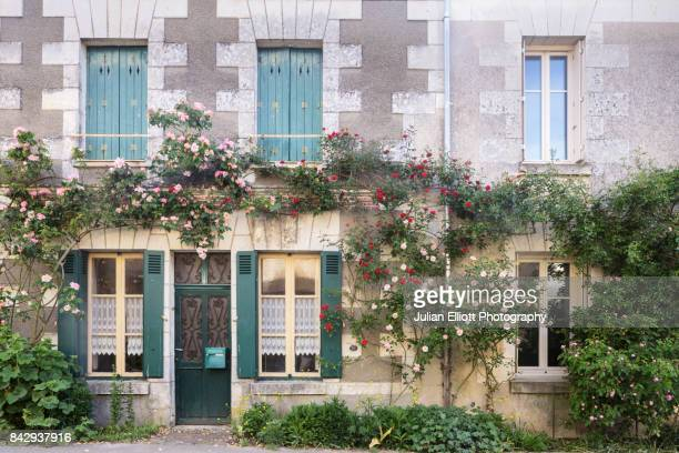 a rose covered house facade in chedigny, france. - chedigny photos et images de collection