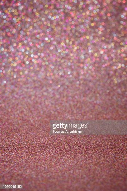 rose gold or red glitter full frame shiny abstract background with vignetting, shallow depth of field. - ローズゴールド ストックフォトと画像