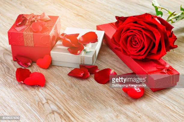 Rose, hearts with Gift box and red ribbon on wood board, Valentines background, wedding day. Love Concept. Valentines day Card with red hearts on wooden background. Soft focus
