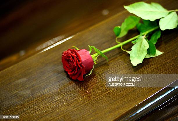 A Rose is displayed on a coffin in an hangar of Lampedusa airport on October 5 2013 after a boat with migrants sank killing more than hundred people...