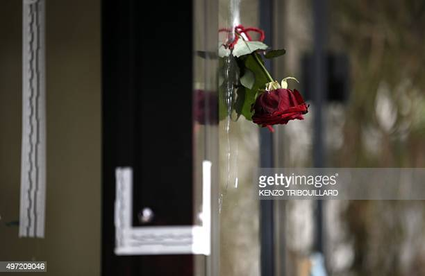 A rose is pictured in a bullet hole in the window of a Japanese restaurant next to the cafe 'La Belle Equipe' Rue de Charonne on November 15 2015 in...