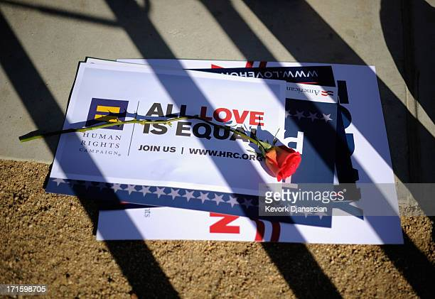 A rose is placed on a sign as people celebrate the US Supreme Court ruling during a community rally on June 26 2013 in West Hollywood California The...