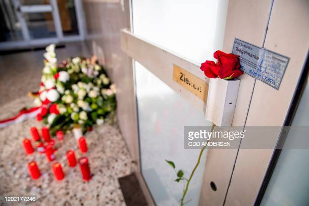 Rose is seen on the door handle at the entrance to Arena Bar and Kiosk placed there for the victims of the Hanau shooting next to a police crime...