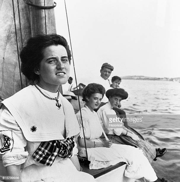 Rose Kennedy at a sailing party. Several young women in long dresses sit on the side of a sailboat.