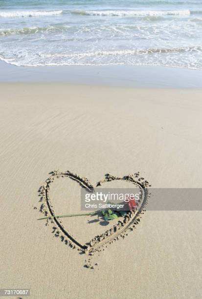 Rose laid on heart drawn in sand