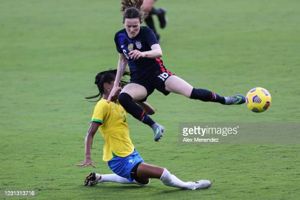 Rose Lavelle of United States leaps over the tackle of Bruna Benites of Brazil during the second half of the SheBelieves Cup at Exploria Stadium on...