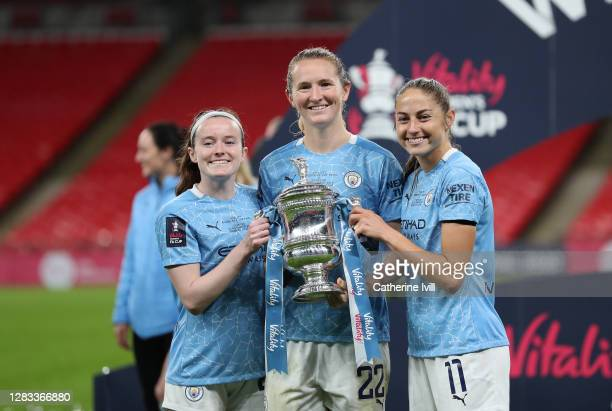 Rose Lavelle, Sam Mewis and Janine Beckie of Manchester City celebrate with the Vitality Women's FA Cup Trophy following their team's victory in the...