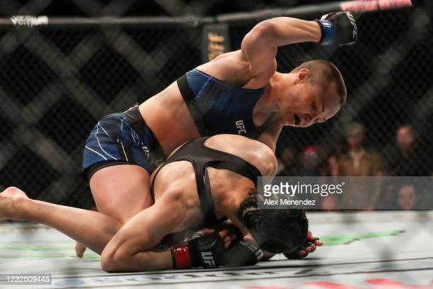 Rose Namajunas of the United States punches Zhang Weili of China during the Women's Strawweight Title bout of UFC 261 at VyStar Veterans Memorial...