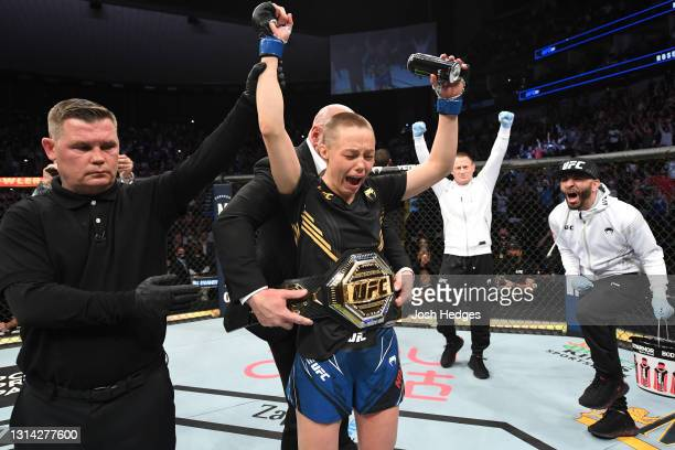 Rose Namajunas reacts after defeating Zhang Weili of China in their UFC women's strawweight championship bout as UFC President Dana White places the...