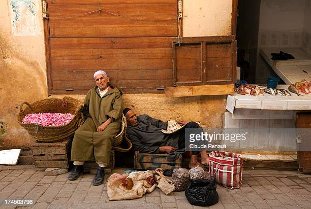 CONTENT] A rose petal seller and a chicken seller during the mid day hot hours in a street of the Fez medina