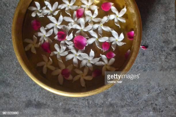 Rose petals and star jasmine flowers in brass urli/decoration