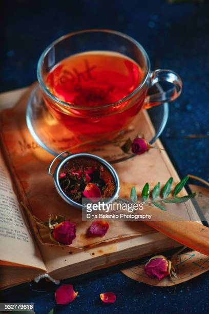 Rose petals herbal tea. Teacup with a strainer on an open book. Dark drink photography concept.