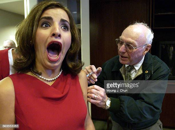 Rose Queen Alexandra Wucetich reacts to a flu shot given by doctor Ray George Tuesday morning at the Tournament House in Pasadena Dr George is a...