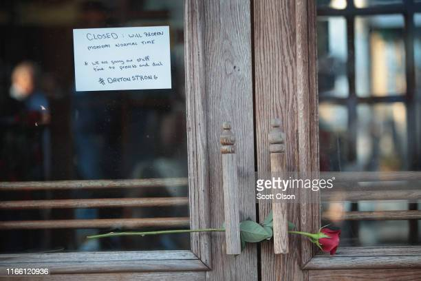 Rose sits in the door at the entrance of Ned Peppers bar in the Oregon District before the start of a memorial service to recognize the victims of a...