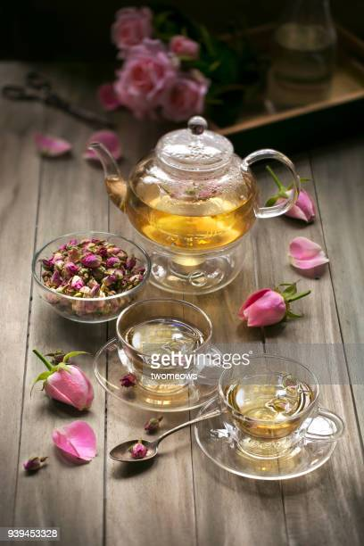 Rose tea in decorative cup on wooden table top.