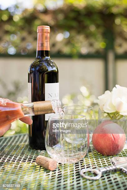 rose wine being poured from a wine bottle into a glass. - wine cork stock photos and pictures