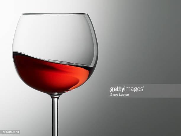 a rose wine swirls in a glass - ワイングラス ストックフォトと画像