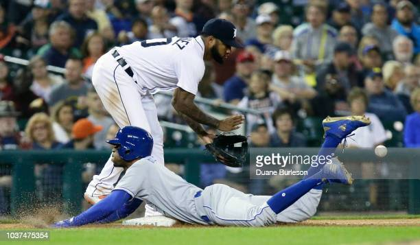Rosell Herrera of the Kansas City Royals dives into third base with a triple beating the throw to Ronny Rodriguez of the Detroit Tigers during the...