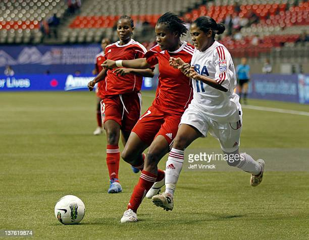 Roselord Borgella of Haiti and Rachel Pelaez of Cuba race to the ball during the 2012 CONCACAF Women's Olympic Qualifying Tournament at BC Place on...