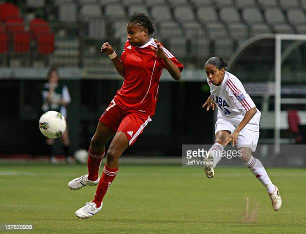 Roselord Borgella of Haiti plays the ball in front of Rachel Pelaez of Cuba race to the ball during the 2012 CONCACAF Women's Olympic Qualifying...
