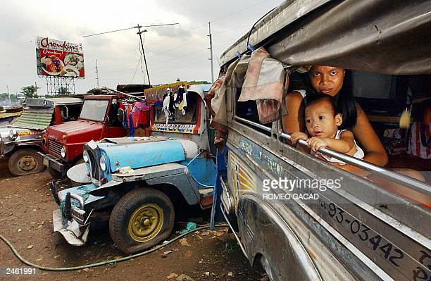 Rosemarie Mapanao cradles her nine months old baby boy John Paul inside their sheltered jeeps in a junkyard of abandoned vehicles along the main...