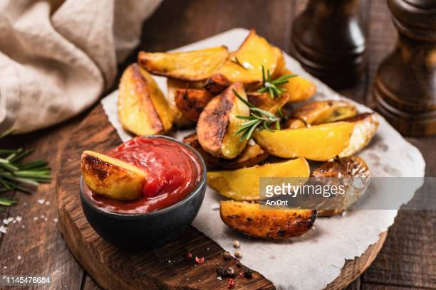 rosemary baked potato wedges with ketchup - prepared potato stock pictures, royalty-free photos & images