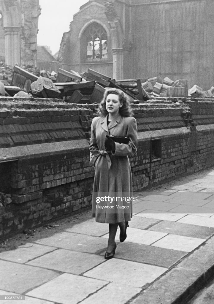 Rosemary Davidson walks home past a bomb-damaged church in Fulham, London, April 1942. Earlier in the day, she had played the role of Britannia in a fund-raising pageant in aid of Warship Week. Original publication: Picture Post - A Day In The Life Of A Warship Week Britannia - Pub. 11th April 1942