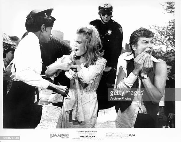 Rosemary Forsyth and Dick Van Dyke approached by the police in a scene from the film 'Some Kind Of Nut' 1969