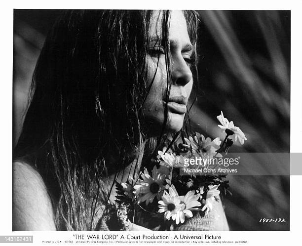 Rosemary Forsyth holding flowers in a scene from the film 'The War Lord' 1965