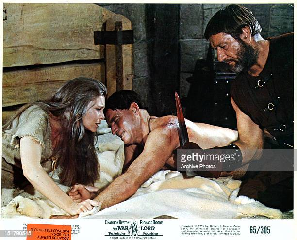 Rosemary Forsyth holding onto Charlton Heston as he's scalded by Richard Boone in a scene from the film 'The War Lord' 1965