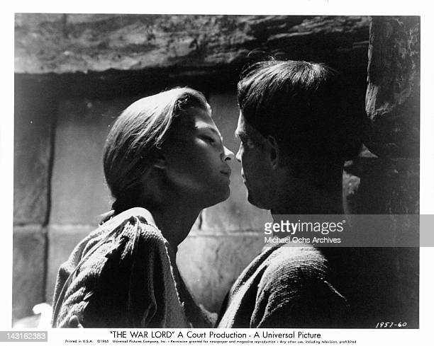 Rosemary Forsyth leans in to kiss Charlton Heston in a scene from the film 'The War Lord' 1965