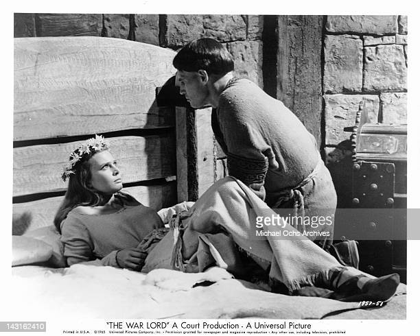 Rosemary Forsyth looking up from the bed at Charlton Heston in a scene from the film 'The War Lord' 1965