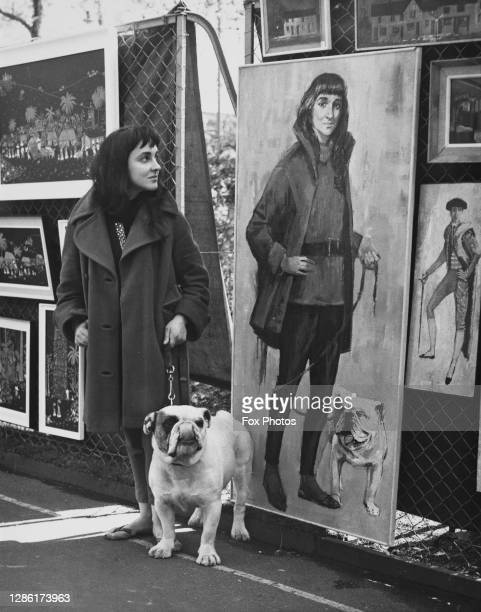 Rosemary Harrison and her pet bulldog, Blockbuster Timbo, standing beside their portrait, painted by Deborah Jones, on display at the London County...
