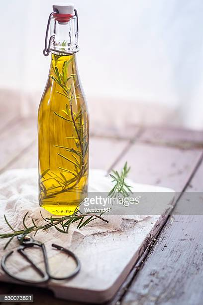 rosemary oil, rosemary twig in olive oil - olive oil stock pictures, royalty-free photos & images