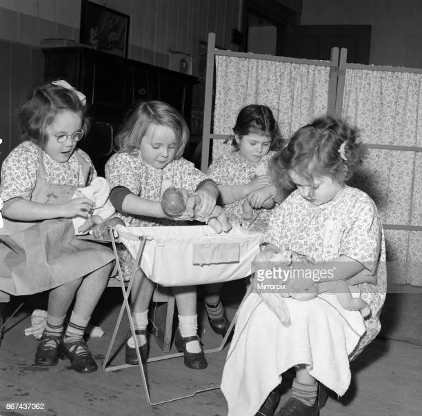 Rosemary Street Nursery School, Bristol. When it is cleaning day at the nursery, the girls have a bath day for their dollies. These four little maids...