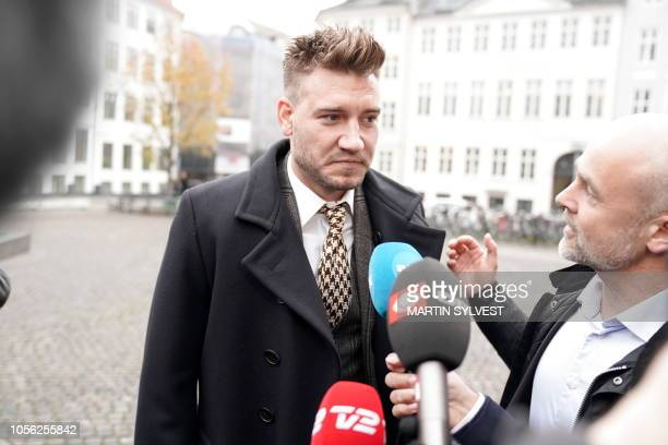 Rosenborg's Danish football player Nicklas Bendtner and lawyer Anders Nemeth talk to the media as they arrive for a hearing at Copenhagen City...